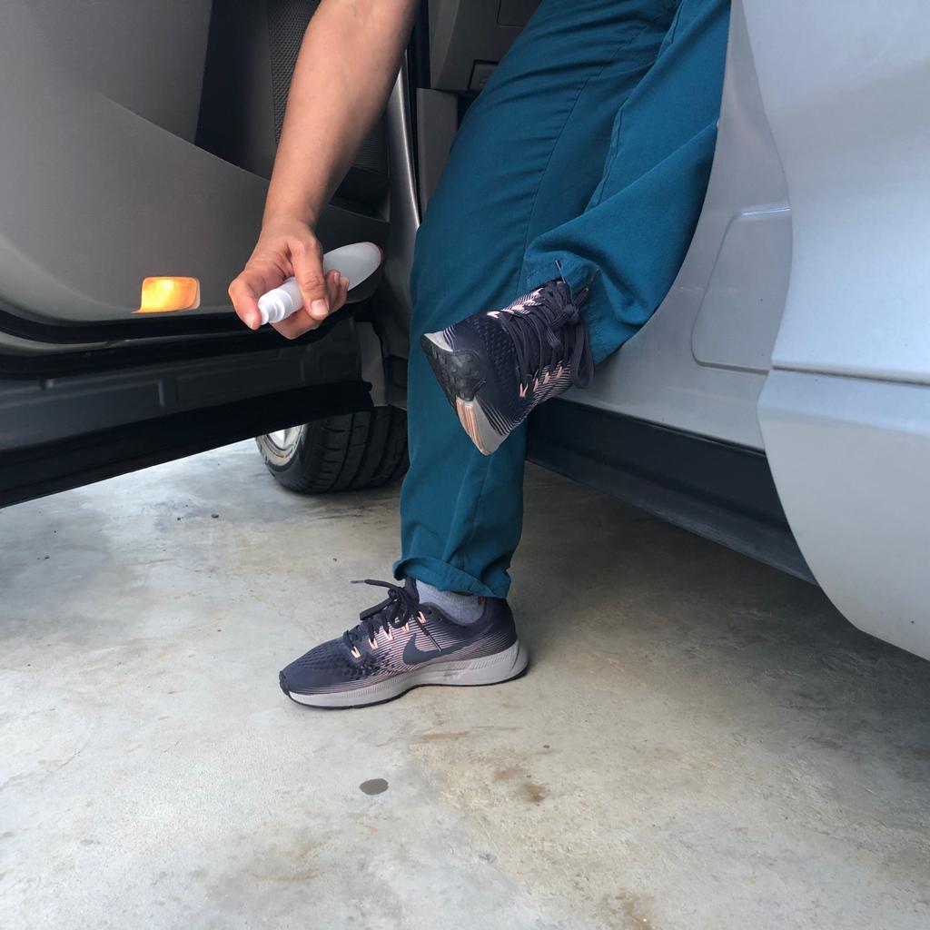 Empleado de salud desinfectando sus zapatos antes de bajarse de su carro